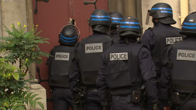 Exterior shots of armed police in riot gear crowbarring open the door of a church in St Denis on November 18 2015 in Paris France