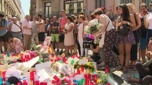 exterior shots of armed police standing on la rambla and people viewing tributes laid at the scene of the terrorist attack in which a van was driven... - terrorism stock videos & royalty-free footage
