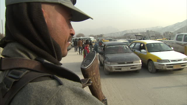 Exterior shots of armed police stopping checking vehicles passengers at a security check point Afghan Police at Security Checkpoint on March 05 2012...