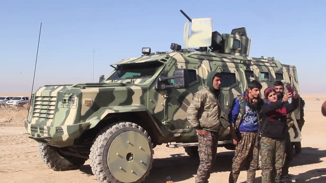 exterior shots of armoured military ypg trucks in the desert and pickup trucks with heavy machine guns parked, as ypg soldiers stand around on 10... - terrorismus stock-videos und b-roll-filmmaterial