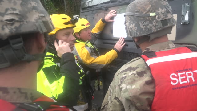 vidéos et rushes de exterior shots of army personnel and firefighers next to an army truck in a flooded street after hurricane florence hit the carolinas on 15 september... - armée de terre