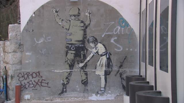 exterior shots of banksy street art in bethlehem israel banksy artwork in israel on september 04 2013 in bethlehem israel - バンクシー点の映像素材/bロール