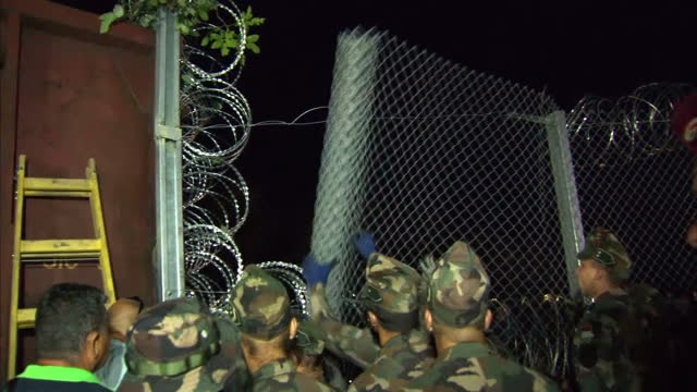 exterior shots of barbed wire fence being delivered to border in roszke and soldiers putting up fence to stop refugees crossing into hungary in an... - hungary stock videos & royalty-free footage