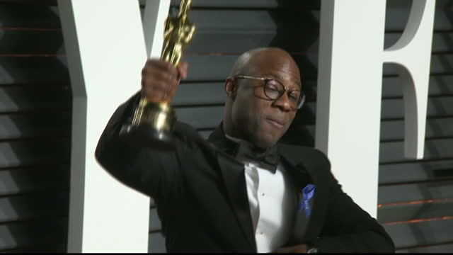 vídeos de stock e filmes b-roll de exterior shots of barry jenkins director of moonlight posing with his oscar award for best picture on the red carpet at the vanity fair oscar party... - festa do óscar