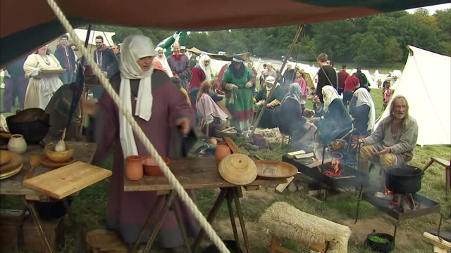 Exterior shots of Battle of Hastings reenactment enthusiasts in period costume cooking weaving clothing and chopping wood on October 15 2016 in...