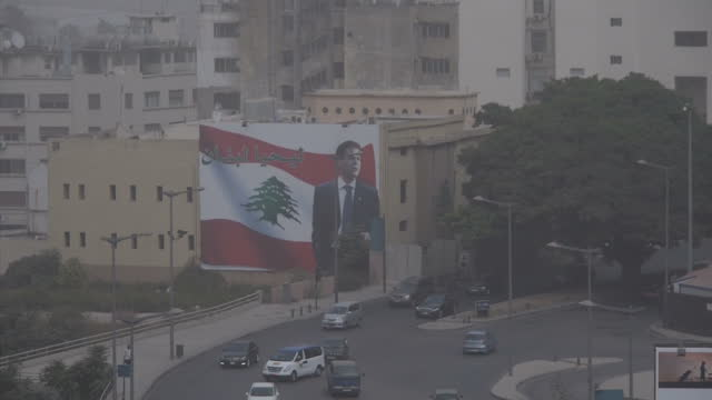Exterior shots of Beirut's port in a severe sandstorm with road intersections cranes and a large poster featuring the image of assassinated Lebanese...