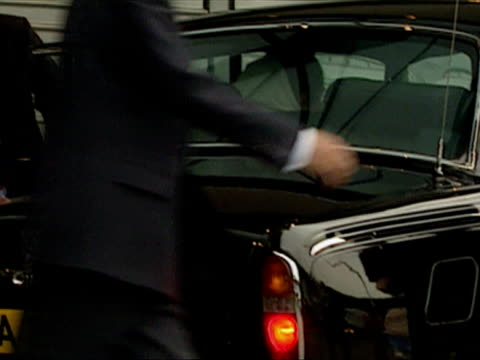 exterior shots of benazir bhutto departing airport and getting into rolls royce car before being driven off with armed police at airport watching on... - rolls royce stock videos & royalty-free footage