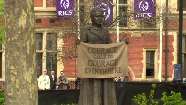 Exterior shots of black cloth being taken off statue to unveil a statue of Dame Millicent Fawcett holding sign 'Courage calls to courage everywhere'...