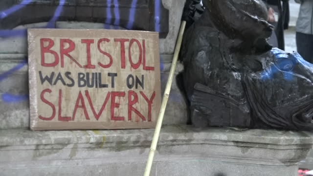 exterior shots of black lives matter protesters standing on top of the plinth where a statue of slave trader edward colston stood earlier that day... - statue stock-videos und b-roll-filmmaterial