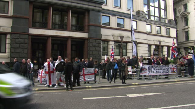 Exterior shots of BNP British National Party EDL English Defence League supporters gathered outside Old Bailey court with posters RESTORE CAPITAL...
