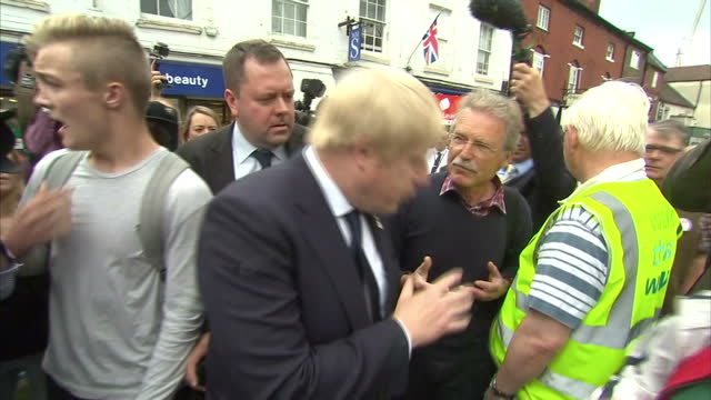 "exterior shots of boris johnson campaigning for ""vote leave"" campaign, surrounded by supporters and a local teenager heckling boris johnson asking... - 2016 european union referendum stock videos & royalty-free footage"