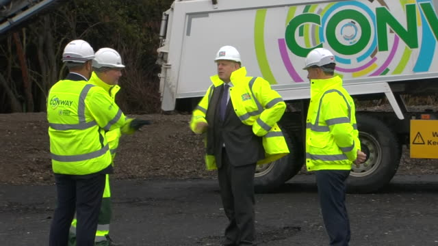 vídeos de stock e filmes b-roll de exterior shots of boris johnson talking to managers on a visit to fm conway asphalt and recycling facility at heathrow wearing high-visibility jacket... - enfeites para a cabeça