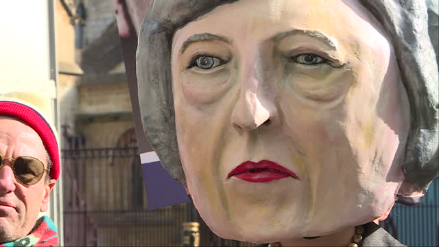 Exterior shots of Brexit protest outside Westminster protesters with black tape crossed over their mouth next to enormous bust of Prime Minister...