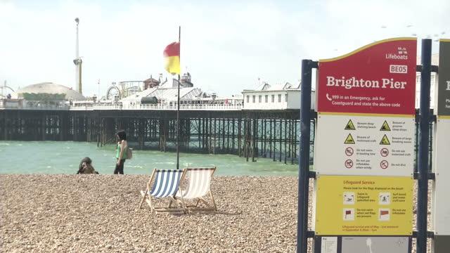exterior shots of brighton pier and a sign warning of swimming dangers on july 21, 2015 in brighton, england. - ブライトン パレスピア点の映像素材/bロール