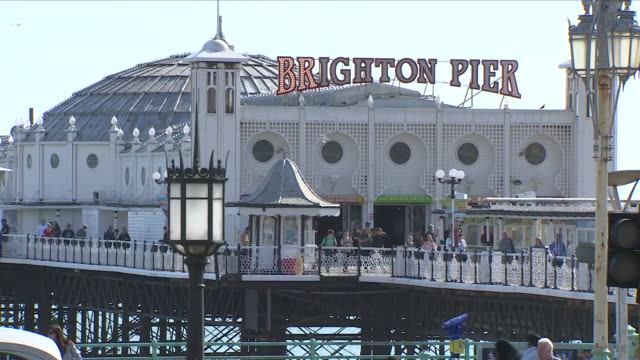 exterior shots of brighton pier on a sunny day, with people walking around and enjoying the sunshine on 18 april 2018 in brighton, united kingdom - イーストサセックス点の映像素材/bロール