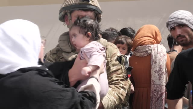 vídeos y material grabado en eventos de stock de exterior shots of british forces helping people gathered outside hamid karzai airport in a desperate attempt to get out of the country, after the... - kabul