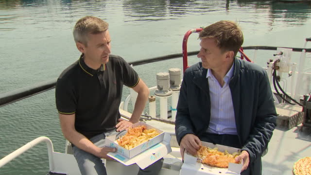 exterior shots of british foreign secretary and conservative party leadership candidate jeremy hunt chatting to fishermen on trawler eating fish and... - 政治家 ジェレミー ハント点の映像素材/bロール