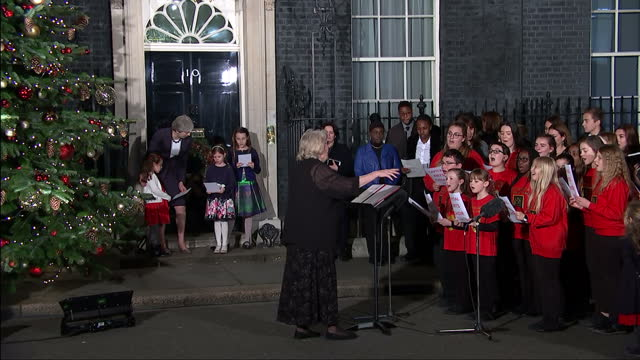 vidéos et rushes de exterior shots of british prime minister theresa may christmas card compitition winners and childrens choir singing carols outside 10 downing street... - choeur