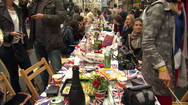 exterior shots of british public sat around at piccadilly street party enjoying the festivities eating cake and drinking with people holding union... - street party stock videos and b-roll footage