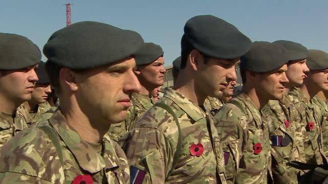 vídeos de stock e filmes b-roll de exterior shots of british troops attending a remembrance service and a union jack flag raised at a british base on november 9 2014 in kandahar... - kandahar