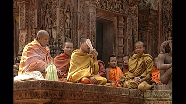 exterior shots of buddhist monks praying outside preah khan temple at angkor wat on april 27th 1998 in phnom penh cambodia - buddismo video stock e b–roll