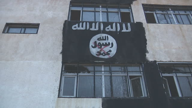 vídeos y material grabado en eventos de stock de exterior shots of buildings covered in isis standards and slogans in a town formerly occupied by the militants now retaken by the kurdish ypg on... - isis
