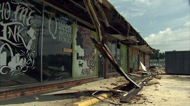 Exterior shots of burnt out strip of shops after rioting in Feguson with a welder making repairs to the roof on August 10 2015 in Ferguson Missouri