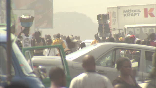 exterior shots of bustling kinshasa with crowds of congolese people walking around carrying groceries and other belongings kinshasa general views on... - コンゴ民主共和国点の映像素材/bロール