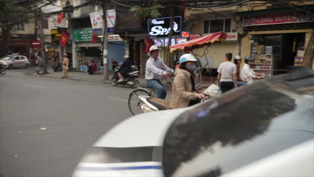 exterior shots of busy traffic along a road in hanoi city centre with scooters pedestrians and cars as policemen watch on and and workers empty... - 首脳会議点の映像素材/bロール