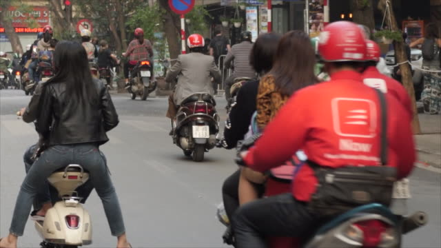 exterior shots of busy traffic along a road in hanoi city centre with scooters pedestrians and cars as policemen watch on on 27 february 2019 in... - 首脳会議点の映像素材/bロール