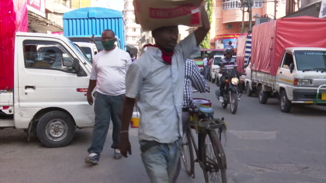 exterior shots of busy traffic and pedestrians in the centre of dar es salaam during the coronavirus pandemic, and people shopping in a busy... - タンザニア点の映像素材/bロール