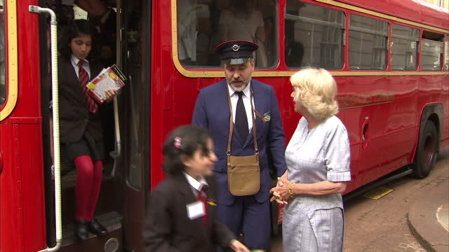Exterior shots of Camilla Duchess of Cornwall greeting schoolchildren arriving on a vintage school bus outside Clarence House and author and comedian...