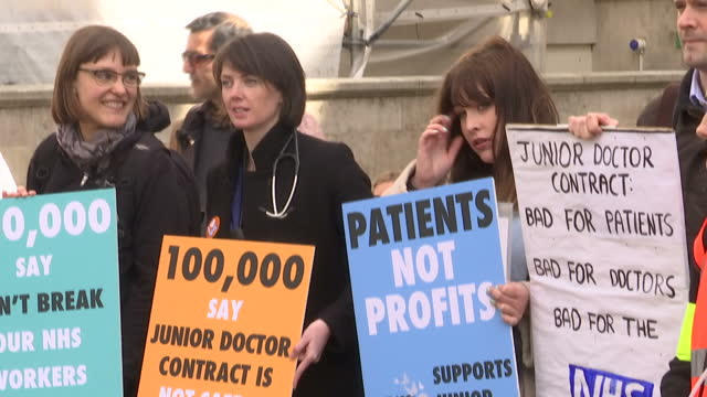 exterior shots of campaigners demonstrating outside the department of health in support of the junior doctors strike holding placards and banners and... - chanting stock videos and b-roll footage