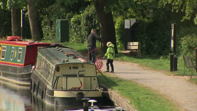 exterior shots of canal in bath people walk along towpath narrow boats in canal below on calm weather day narrow boat moving slowly through water... - somerset england stock videos & royalty-free footage