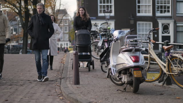 exterior shots of canals, bicycles and people walking over bridges and along pavements on 26 november 2019 in amsterdam, netherlands - amsterdam stock videos & royalty-free footage