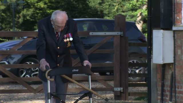 exterior shots of captain tom moore army veteran walking up and down garden path with a walker during his successful bid to raise funds for the nhs... - captain tom moore stock videos & royalty-free footage
