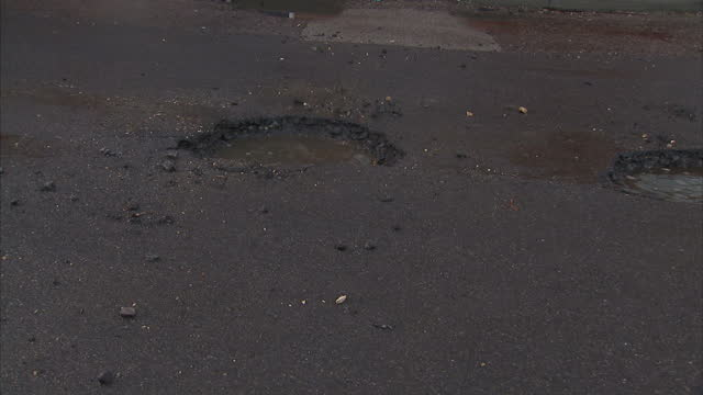 vídeos de stock, filmes e b-roll de exterior shots of car driving slowly through big potholes in road, water filed on in colchester, england. - caldeirão água parada