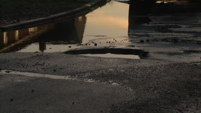 Exterior shots of car driving through deep bad potholes on bend in road filled with water on in Colchester England