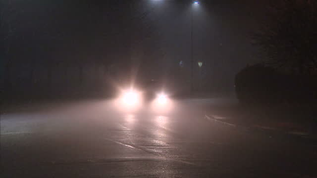 exterior shots of cars passing a mini roundabout in osterley in freezing fog in the dark early morning on december 30, 2016 in london, england. - fog stock videos & royalty-free footage