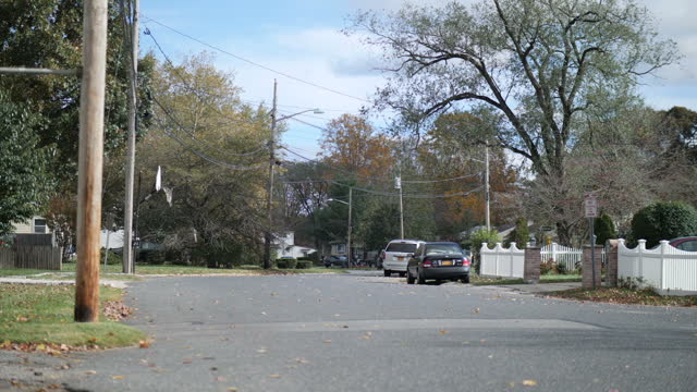 exterior shots of cars passing along a suburban residential road as autumn leaves fall on 12 december 2017 in brentwood new york united states - porta della cella video stock e b–roll