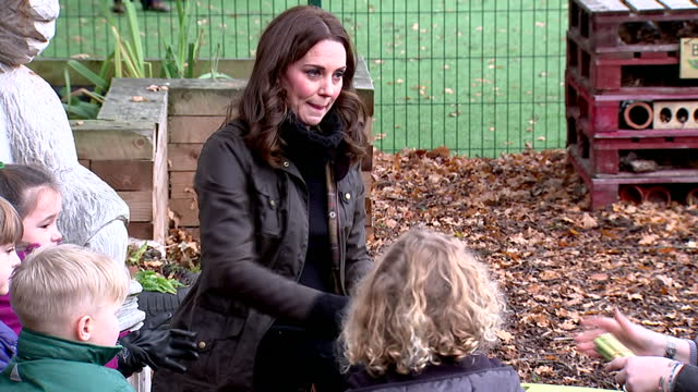 exterior shots of catherine duchess of cambridge joining in with pupils taking part in a stick whittling activity at robin hood primary school before... - herzogin stock-videos und b-roll-filmmaterial