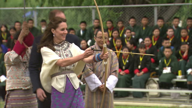 exterior shots of catherine duchess of cambridge shooting an arrow at a target with a bow and arrow, prince william cheering on april 14, 2016 in... - bhutan stock videos & royalty-free footage