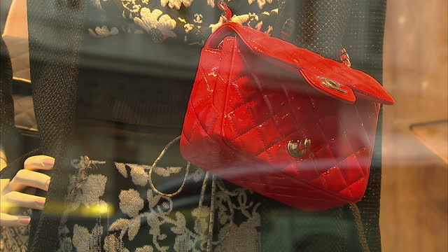 exterior shots of chanel signage and a red, quilted chanel handbag on display in a shop window at a chanel store on new bond street. designer brand... - bag stock videos & royalty-free footage