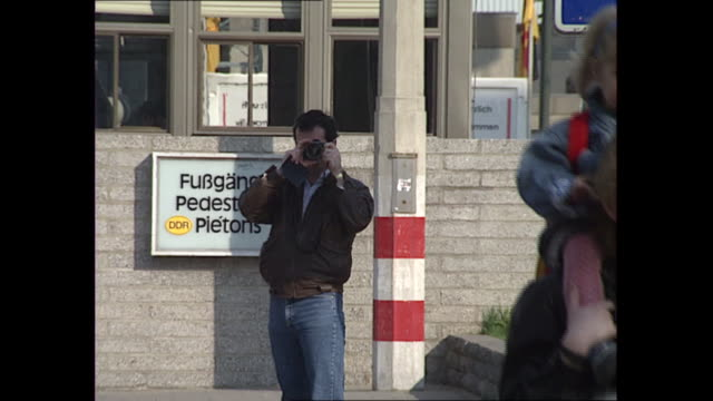 exterior shots of checkpoint charlie in the wake of re-unification, with a barrier and signs as cars pass guards, and souvenier sellers selling... - politik und regierung stock-videos und b-roll-filmmaterial
