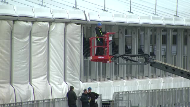 vídeos y material grabado en eventos de stock de exterior shots of cheltenham race course as workmen make preparations to the main enclosure and jockeys file past on horseback on 13 march 2019 in... - apuestas deportivas