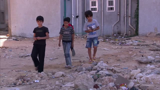 exterior shots of children on refugee housing complex estate walking through rubble and sitting on balcony refugees at syrian housing complex in... - schutt stock-videos und b-roll-filmmaterial