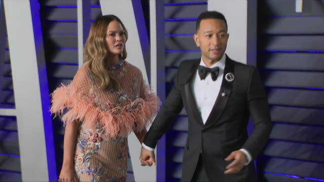 stockvideo's en b-roll-footage met exterior shots of chrissy teigen and john legend posing on the red carpet of the 2019 vanity fair oscar party on 24th february 2019 in los angeles,... - academy awards