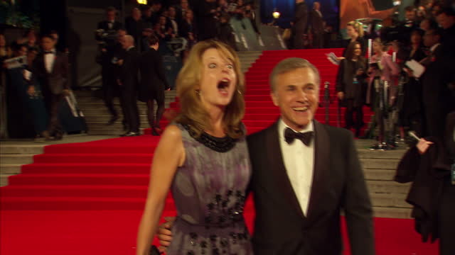 vídeos de stock, filmes e b-roll de exterior shots of christoph waltz with his wife judith holste posing for photo op at the royal world premiere of 'spectre' at royal albert hall on... - james bond trabalho conhecido