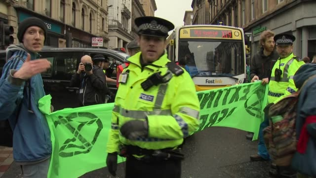 Exterior shots of climate change protesters marching in Glasgow blocking traffic with banners and signs 'Climate Emergency' etc on 2 March 2019 in...