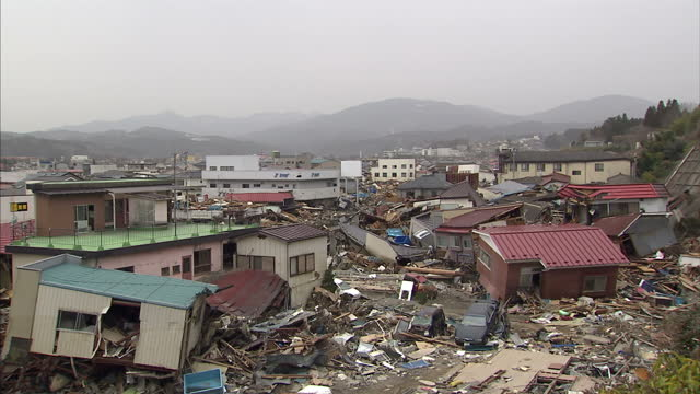 Exterior shots of collapsed and burnt out buildings in the aftermath of the earthquake crushed cars buillding rubble in streets Filmed on March 22...